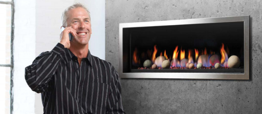 Man talking on phone beside gas fireplace